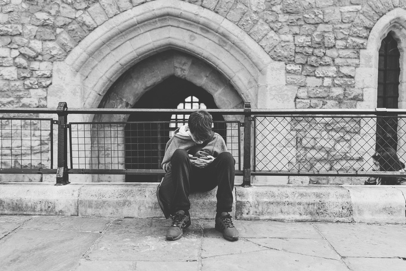 lifestyle photography of a boy on his phone at the tower of london