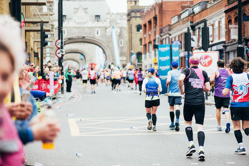 two athletes running to tower bridge wearing faversham running club vests
