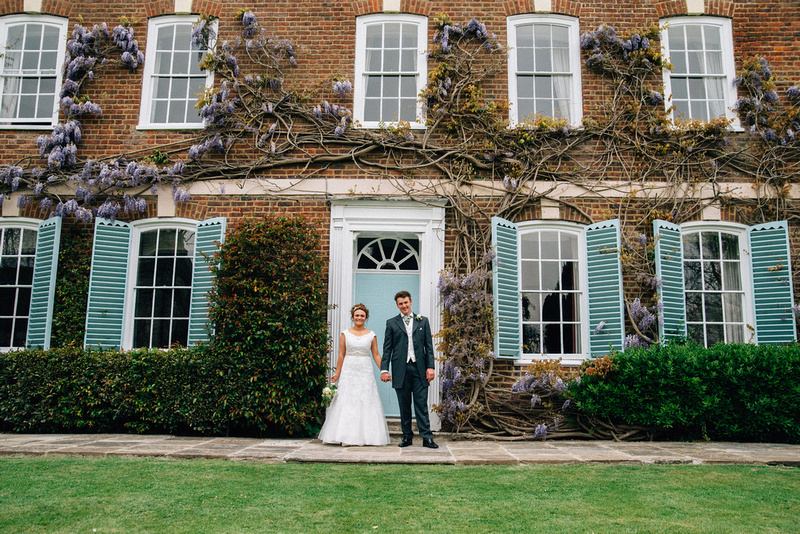 The bride and groom posing in front of a farmhouse during a wedding in canterbury