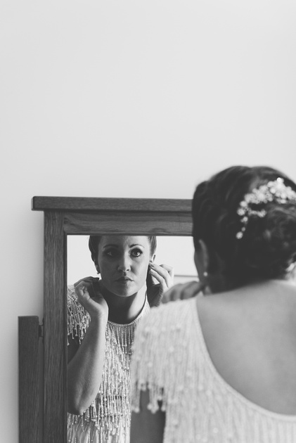 A bridesmaid looking into a mirror before a farm wedding in Canterbury