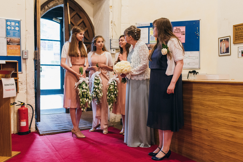 Bride and bridesmaids waiting before the wedding at St. Marys Church Chartham