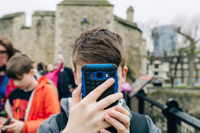a boy taking a photo at the tower of london